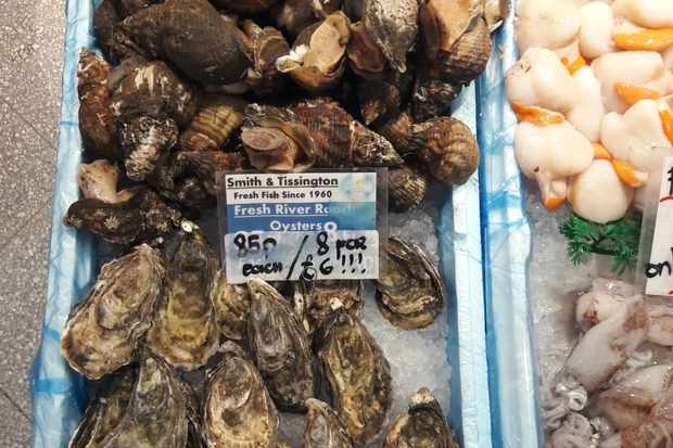 A fishmongers in Sheffield's Moor Market has a tray lined with fresh oysters