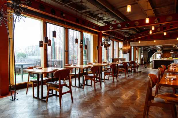 A dining room is complete with parquet flooring and wooden tables for two. There are floor to ceiling glass windows looking out over the city of Manchester
