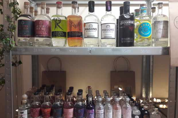 A metal case is lined with bottles of British gin