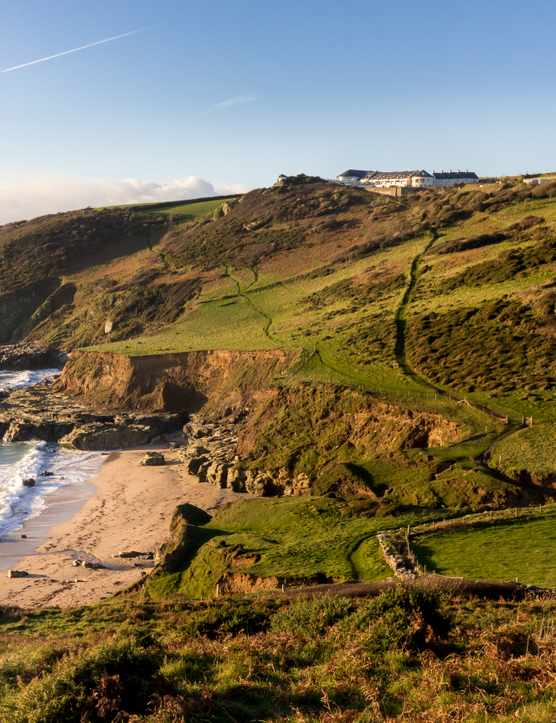 Gara rock hotel can be seen in the distance, set on a cliff in Devon overlooking the coast