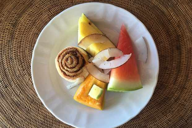 A white circular plate is topped with a slice of watermelon, slice of pineapple, slices of coconut and a swirly cinnamon bun