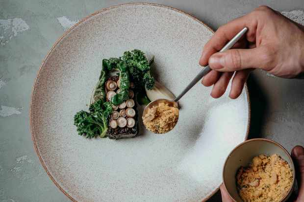 A pale grey speckled plate is topped with a piece of short rib beef. On top of the beef are perfectly placed shimeji mushrooms each in a row of three. There is chard and a quenelle of artichoke puree