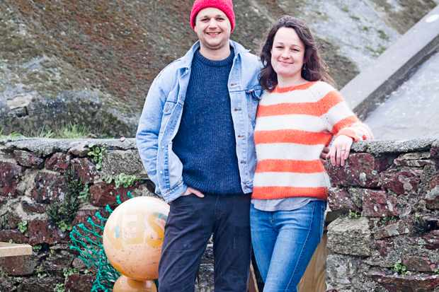 On a pebble beach a couple stand together, the woman is wearing an orange and white striped jumper and the man is wearing a blue jumper, denim jacket and red hat