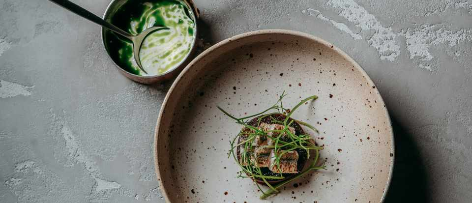A speckled bowl is filled with cubes of yakitori-smoked mackerel with beetroot, trout roe and herbs. There is a small pan in the background with the remains of a green sauce in