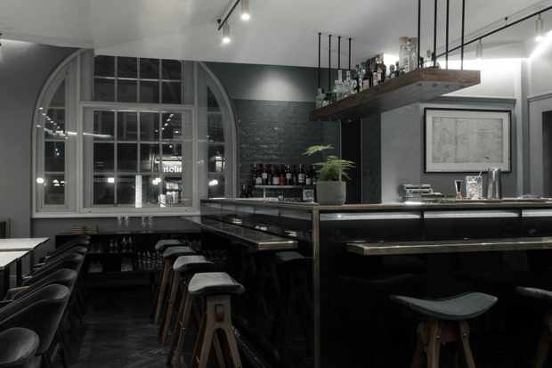A restaurant has a central bar with bar stools dotted around the edge. There is a curved Victorian window