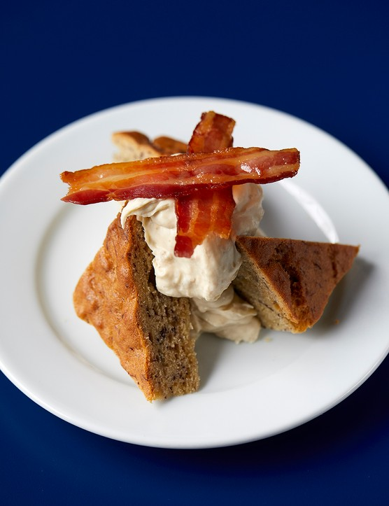 Two triangular pieces of chocolate chip banana bread with lots of maple cream dolloped on top, with two crisp rashers of bacon balancing on top
