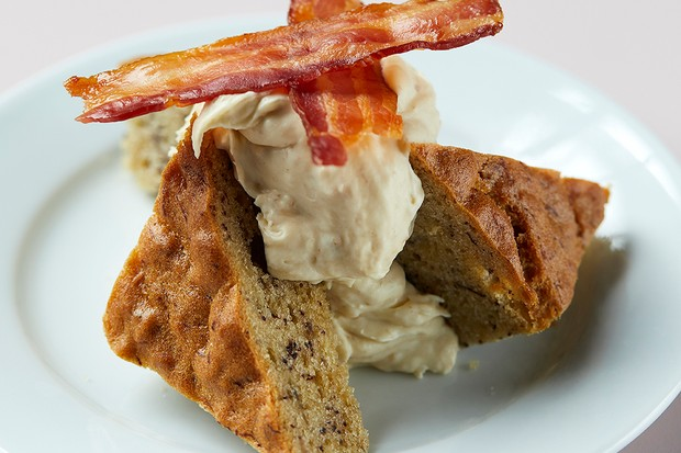 A pale blue plate is topped with two triangular chunks of banana bread. They are topped with a large dollop of maple cream and two crisp rashers of bacon