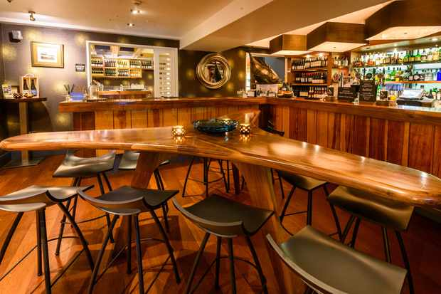 A restaurant has wooden panelled walls and a long wooden bar with black high stools
