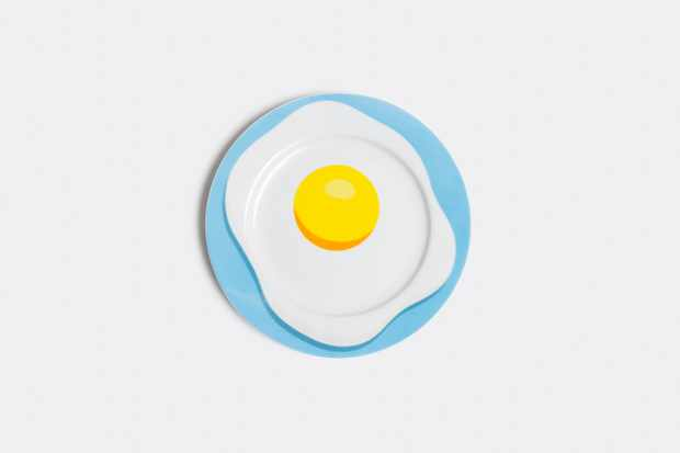 A pale blue plate with a painting of a fried egg on top