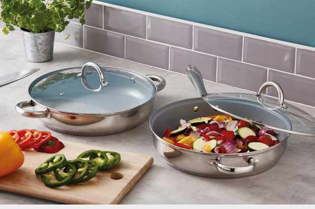 A kitchen counter is topped with two silver saute pans. In one pan is chopped vegetables, and the other one is empty. There is also a chopping board with sliced peppers on top
