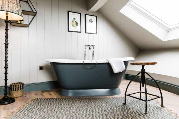 A bathroom at the Gara Rock Hotel has white-washed, wooden panelled walls. There is a dark grey freestanding bath with a towel perched on the side and a small wooden table to one side
