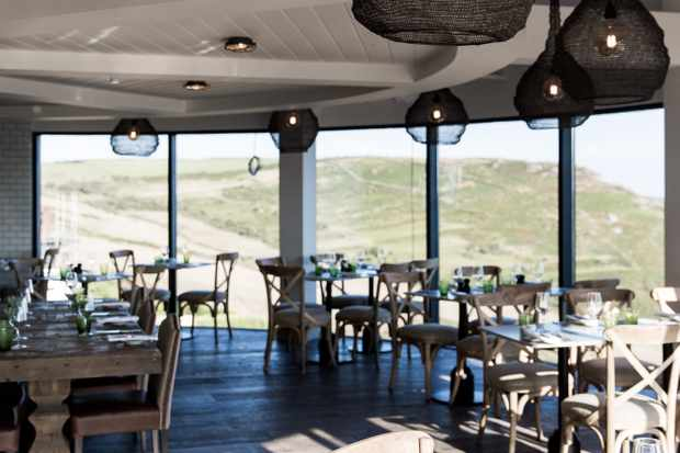 The restaurant at Gara Rock has curved floor-to-ceiling glass windows that look out over the Devon cliffs