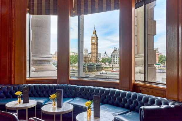 Blue leather booth seats next to a window with views of Big Ben