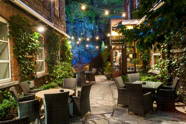 A courtyard has tables and chairs and is strung with fairy lights. In the background is a waterfall