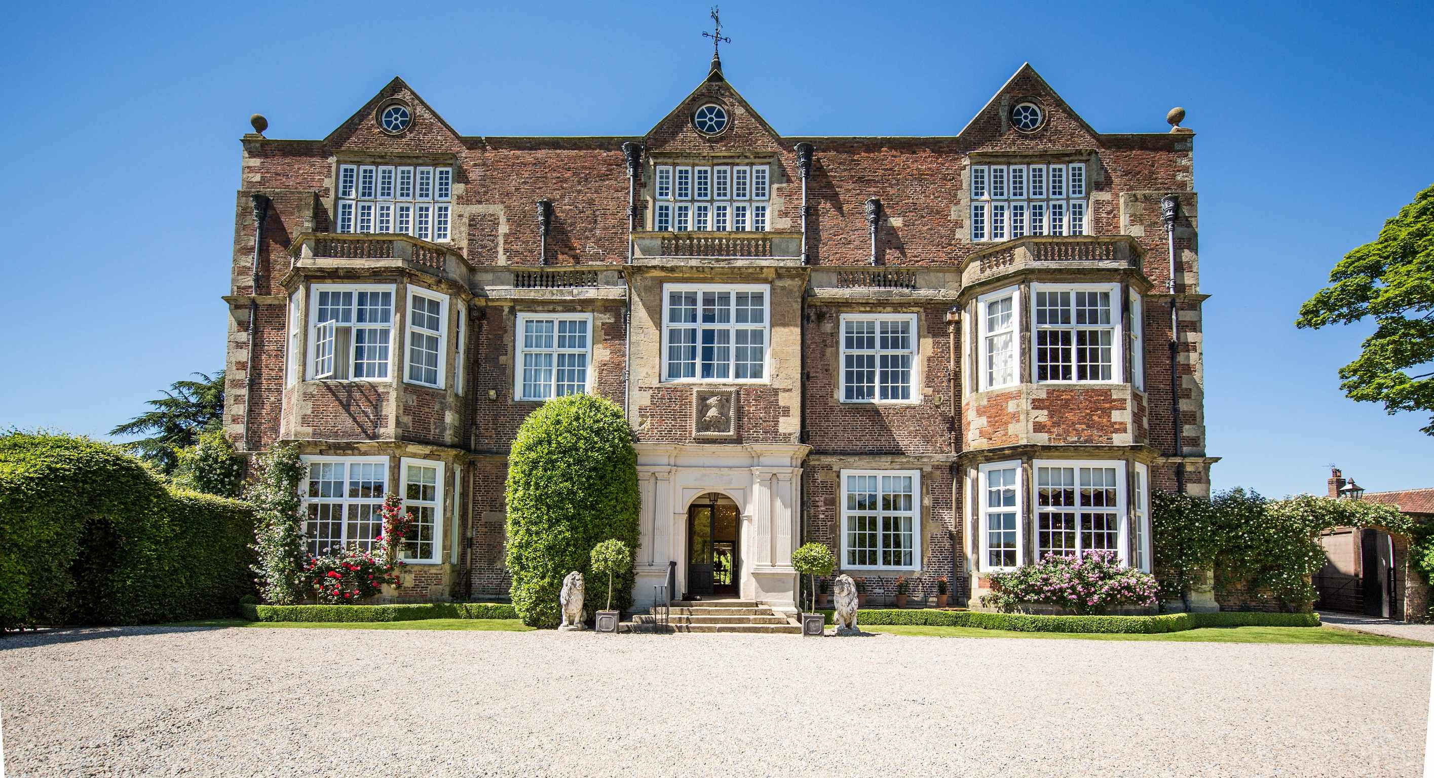 The exterior of Goldsborough Hall, Yorkshire. A striking Grade II listed building has a large driveway leading up to it with tress outside