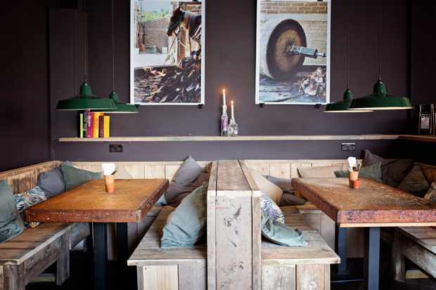A dark grey wall has two photos hanging on it. In front of the wall and two wooden tables with long booth seats with cushions on