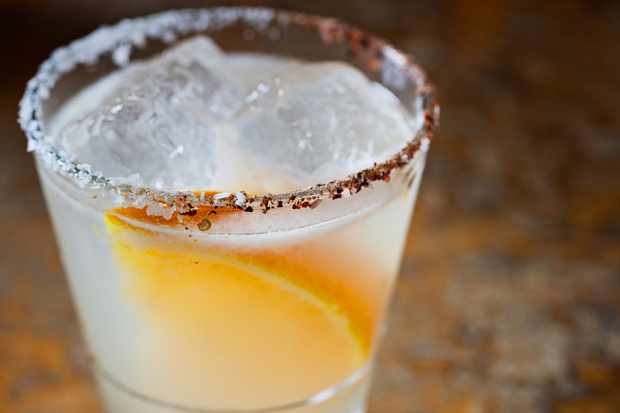 A small glass is filled with a margarita. There is a slice of orange in the glass and the rim of the glass is lined with orange salt