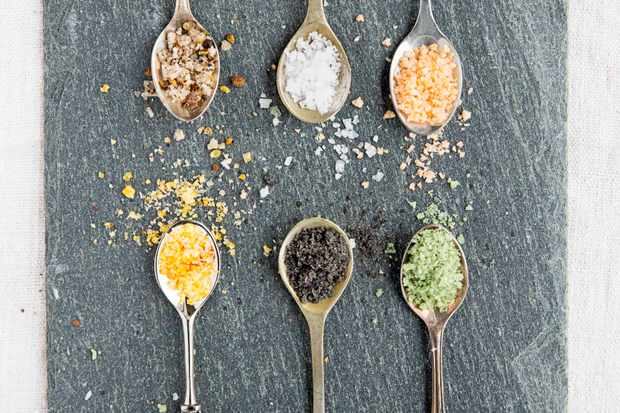 A slate is topped with six small spoons. On each spoon is a colourful selection of sea salt