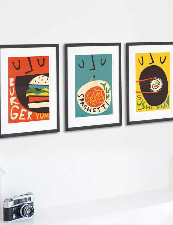 Three food prints in black frames hang on a wall. One is a print of a burger, the next is a bowl of spaghetti and the final one is a sushi roll