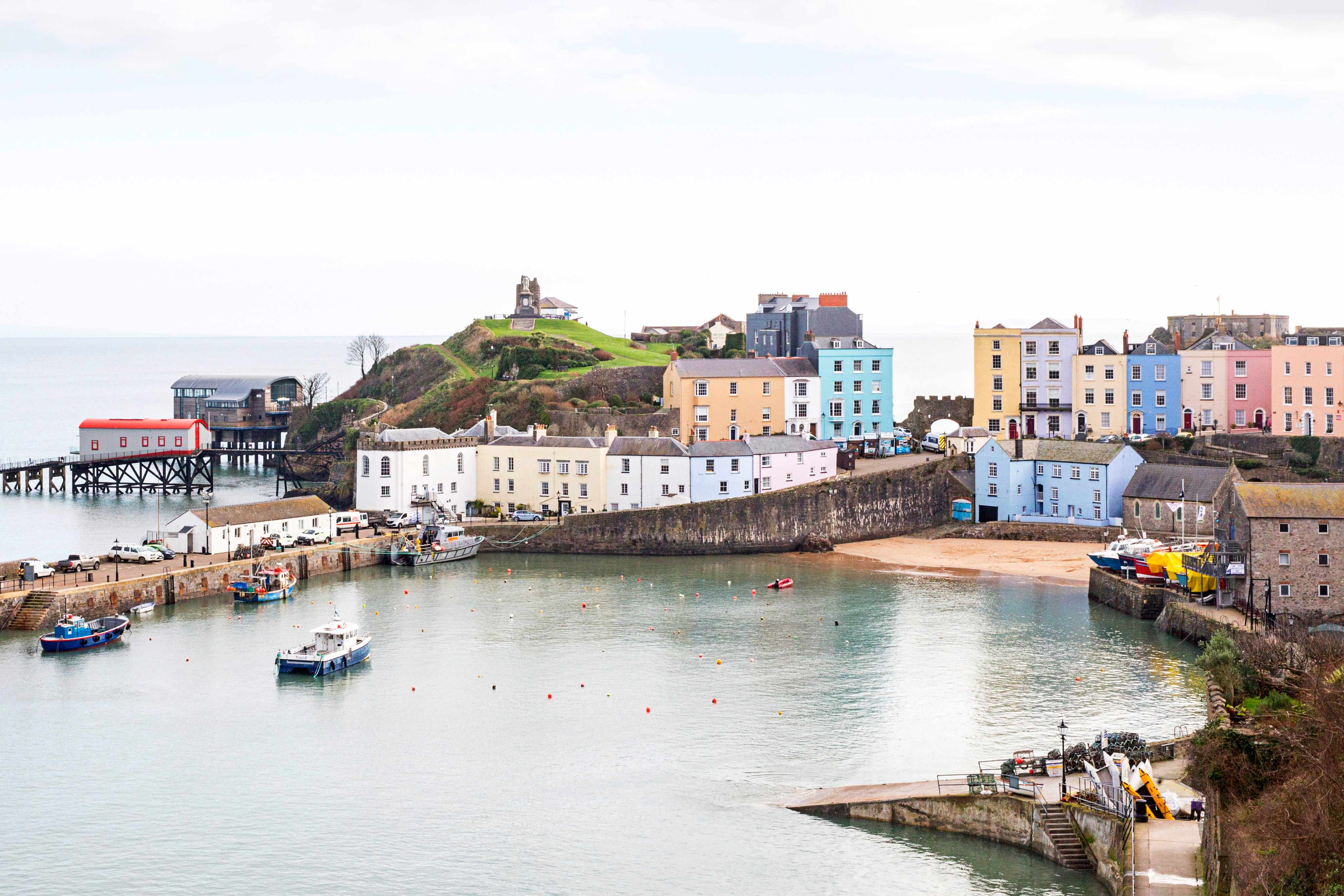 Tenby harbour with pastel coloured houses and a boat in the calm water