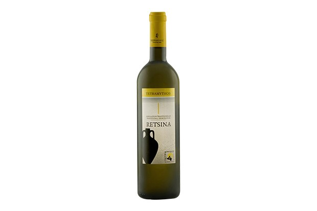 A dark wine bottle is filled with white wine. It has a label on the front with a Greek vase on the label