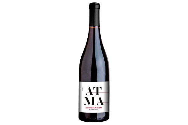 A bottle of red wine with a white label on the front. The label has the letters ATMA written on it in a bold font