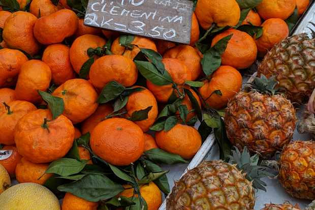 A market stall has a tray of clementines with leaves on and small pineapples