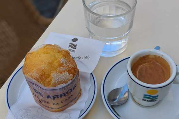 A white table has an espresso, a glass of white and a golden muffin on it