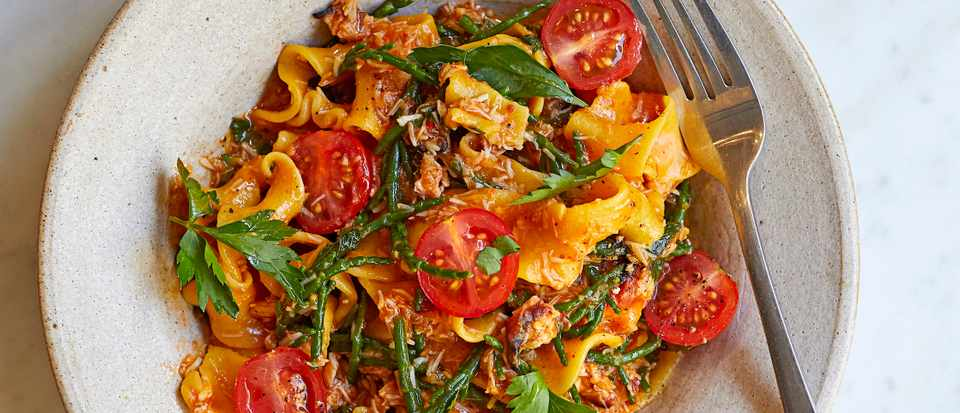 A bowl of fresh pappardelle with crab, samphire and tomatoes