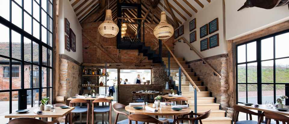 A converted barn with exposed wooden beams, wooden tables and chairs