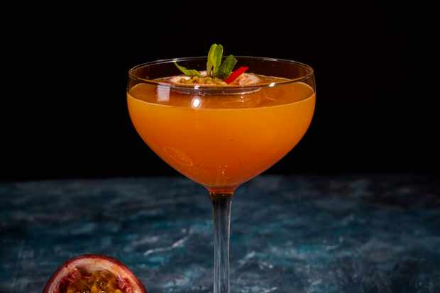 A glass filled with an orange passion fruit martini with half a passion fruit on the side