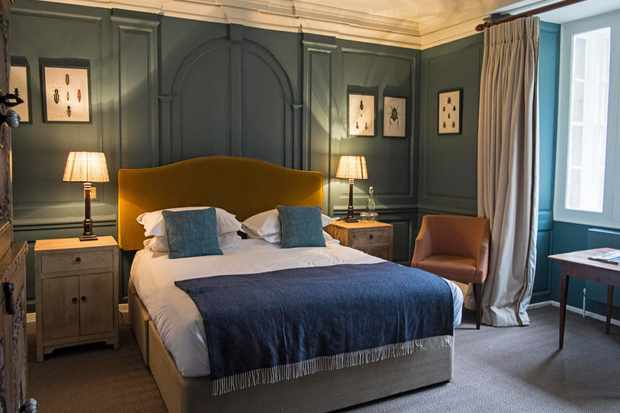 A double bedroom with blue wooden panelled walls and a double bed with a yellow velvet headboard