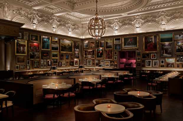 An opulent restaurant with paintings on the walls and booths