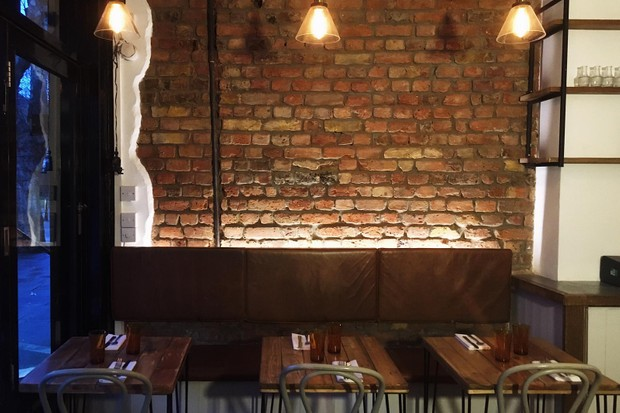 An exposed brick wall with small wooden tables and chairs for two