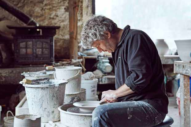 A man in jeans and a fleece is creating pottery. He is in a studio surrounded by clay