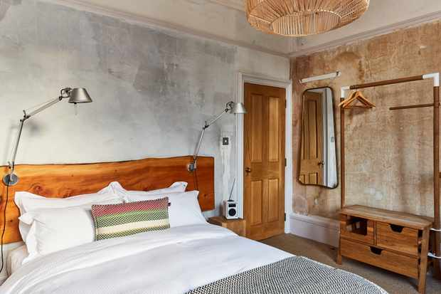 A minimalist room with grey walls, a bed with wooden headboard and long mirror hanging on the opposite wall