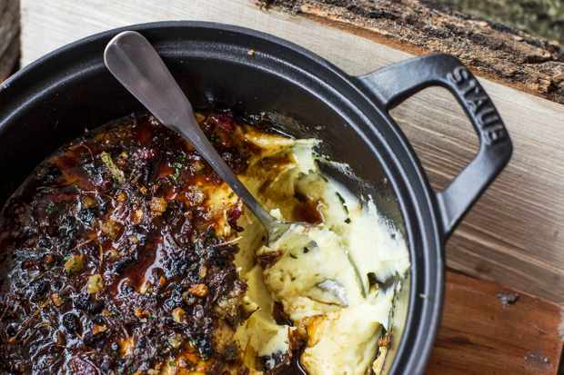 A black cast iron pot filled with creamy mashed potato topped with diced venison