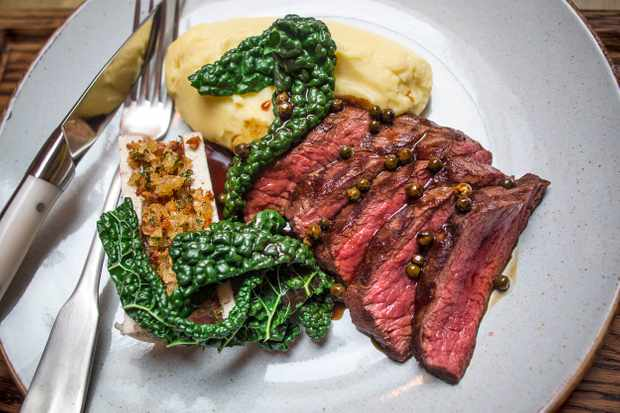 A white plate topped with juicy pink slices of deer, cavolo nero and bone marrow