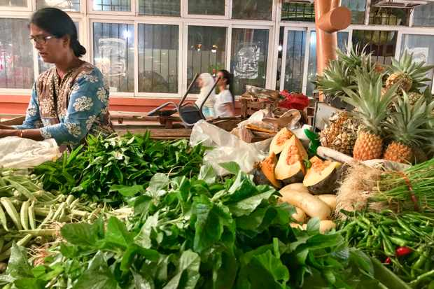 A market stall with woman selling fresh herbs and pineapples