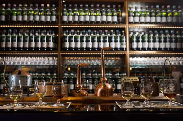 A dark bar with bottles lining the background and glasses of whisky laid out on the bar