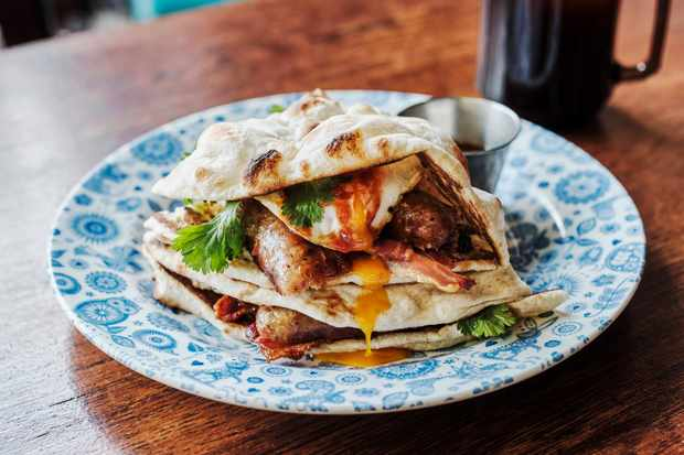 A naan bread is filled with a fried egg, streaky bacon and sausage on a blue and white floral patterned plate