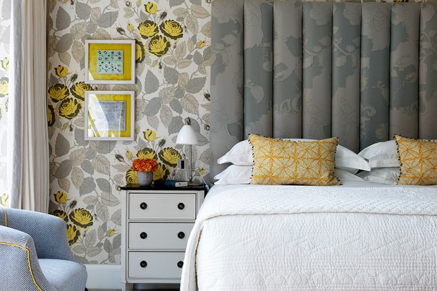 A suite at the Ham Yard Hotel with a double bed, floral wallpaper and an armchair in the corner