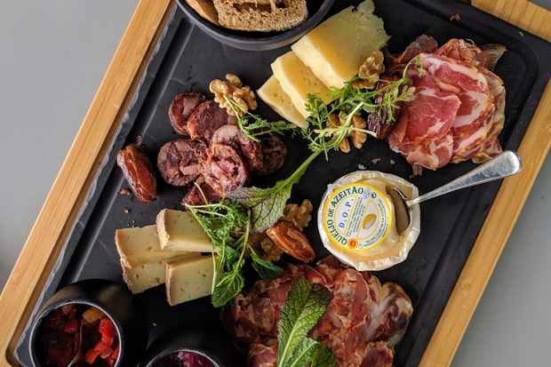 A slate board topped with slices of charcuterie, cheese, dates and walnuts