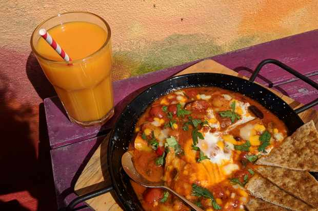 A shallow pan filled with vegetarian shakshuka topped with eggs and a glass of orange juice with a paper straw