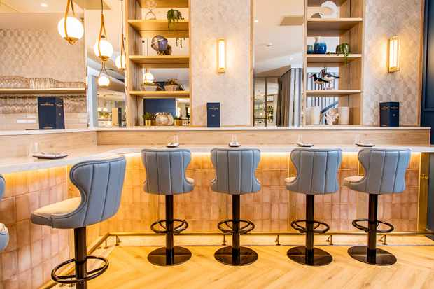 Blue leather stools around the marble bar at The Oyster Club, Birmingham