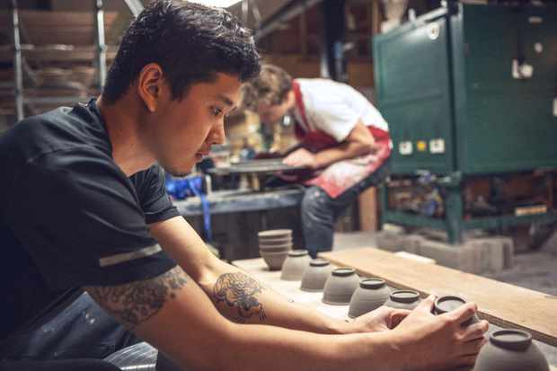 A man is checking pottery while another man works on a potters wheel in the background