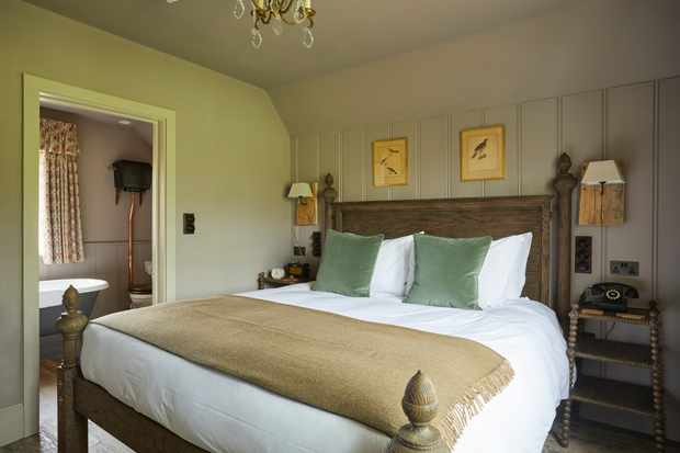 A bedroom with white-washed wooden-pannelled walls. A wooden double bed has white linen and green cushions