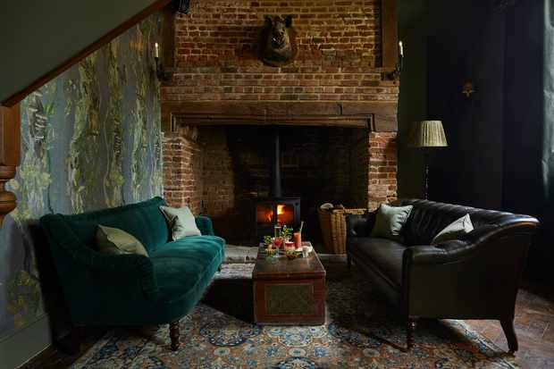 A dimly lit room with wood-burning fire, exposed brick walls and velvet sofas