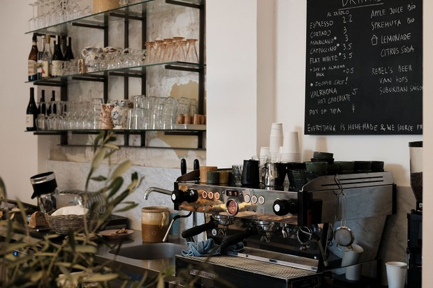 White walls have shelves lined with glasses on them and there is a blackboard with writing on. A large coffee machine is in the foreground of the image