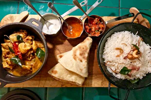 A wooden platter is topped with a bowl of chicken curry, a bowl of rice, tomato chutney and flatbreads